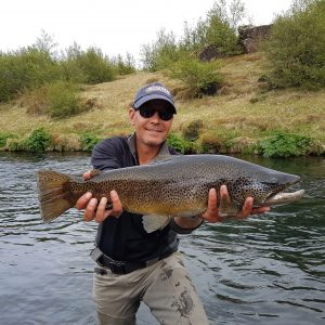 Happy angler with his newly caught Brown trout in a river in Iceland