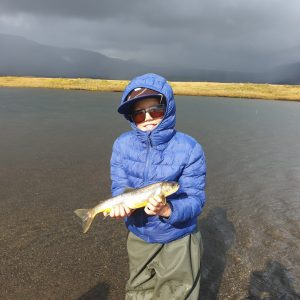 A boy happy with his trout that he caught fishing in Iceland